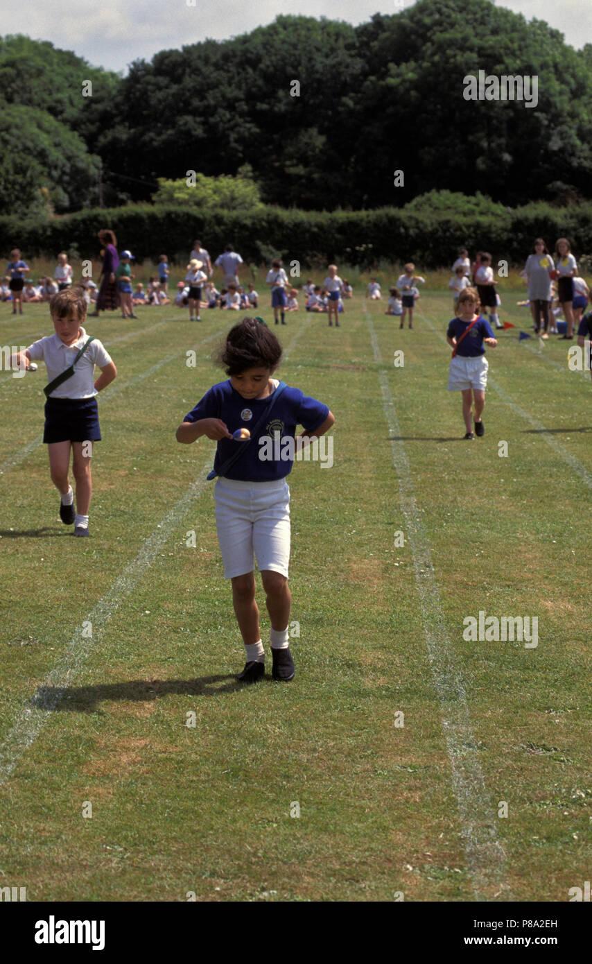 Los niños que participan en el huevo y cuchara carrera en la escuela primaria día deportivo Imagen De Stock