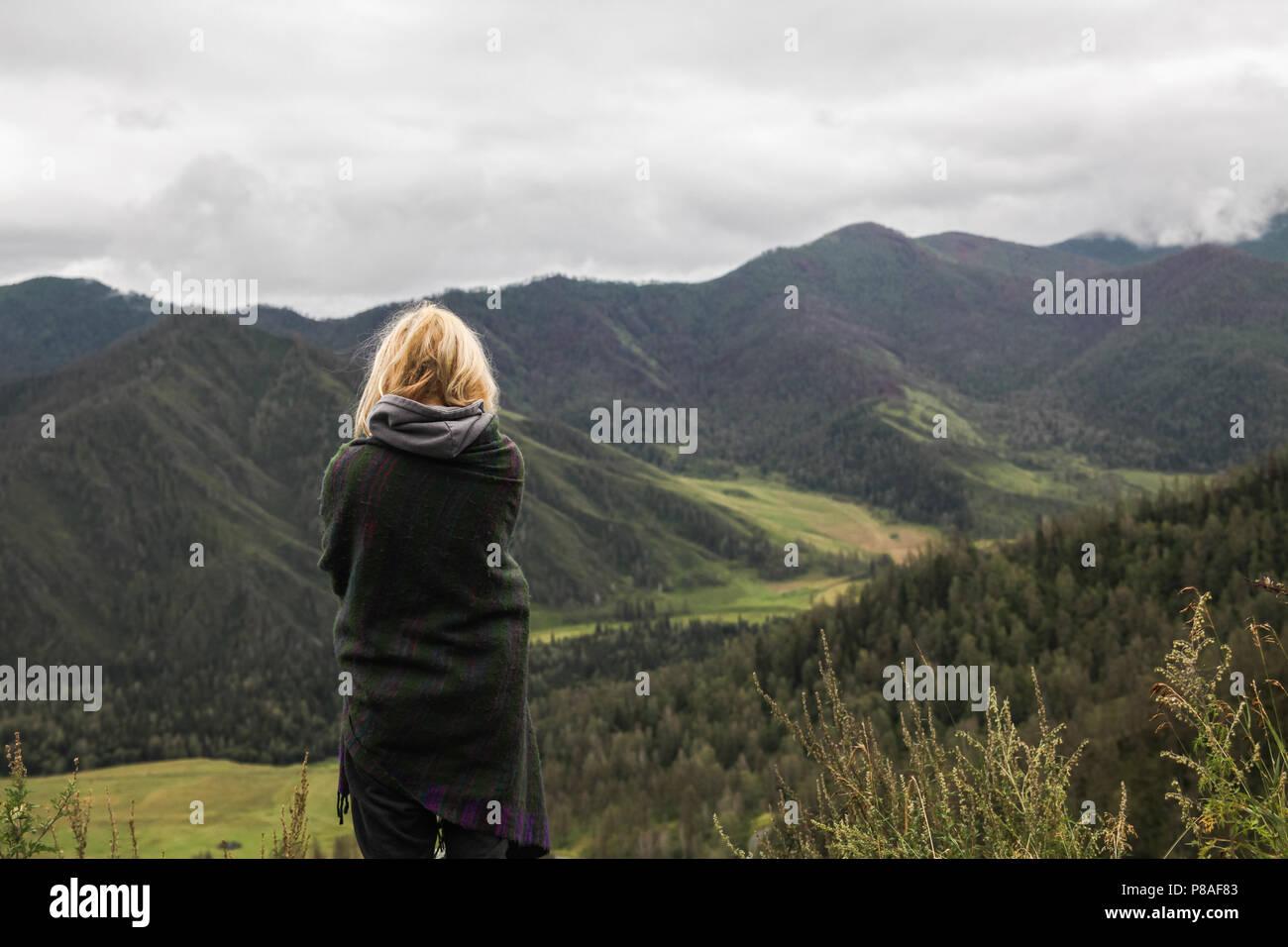 Vista posterior de la joven mujer mirando al hermoso paisaje en las montañas Altai, Rusia Imagen De Stock