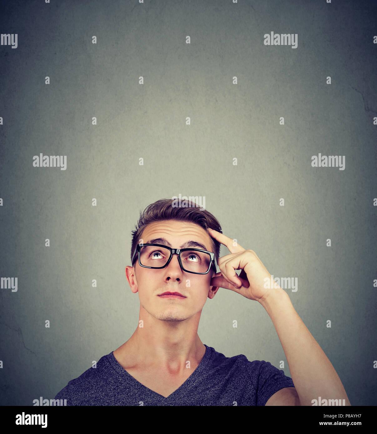 Retrato dudoso pensar joven desconcertado rascándose la cabeza busca una solución aislada, mirando hacia arriba en la pared de fondo. Expresión de cara humana Foto de stock