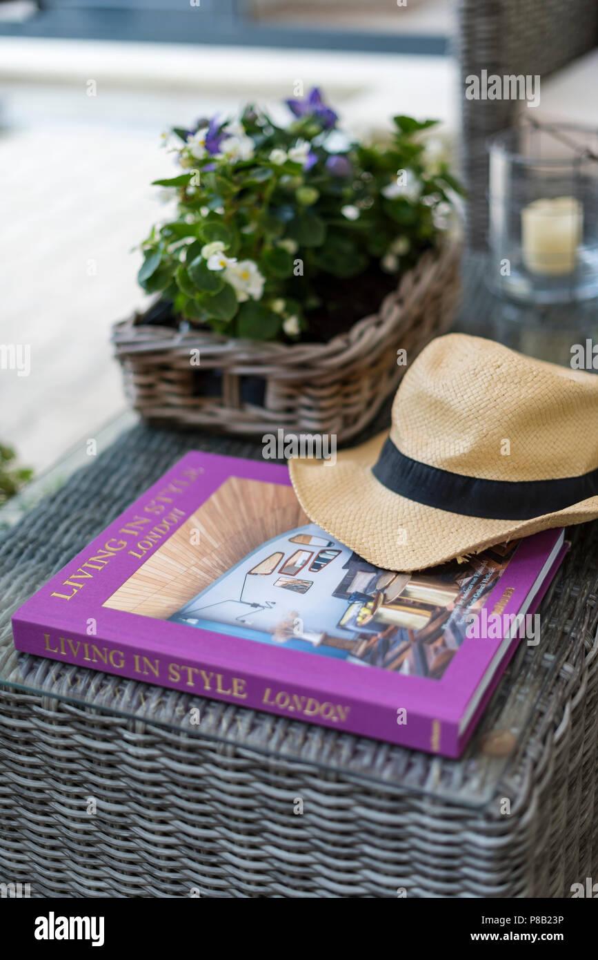 96042784682cb Sombrero para el sol y reserve con plantas en floración en heces de mimbre  en el
