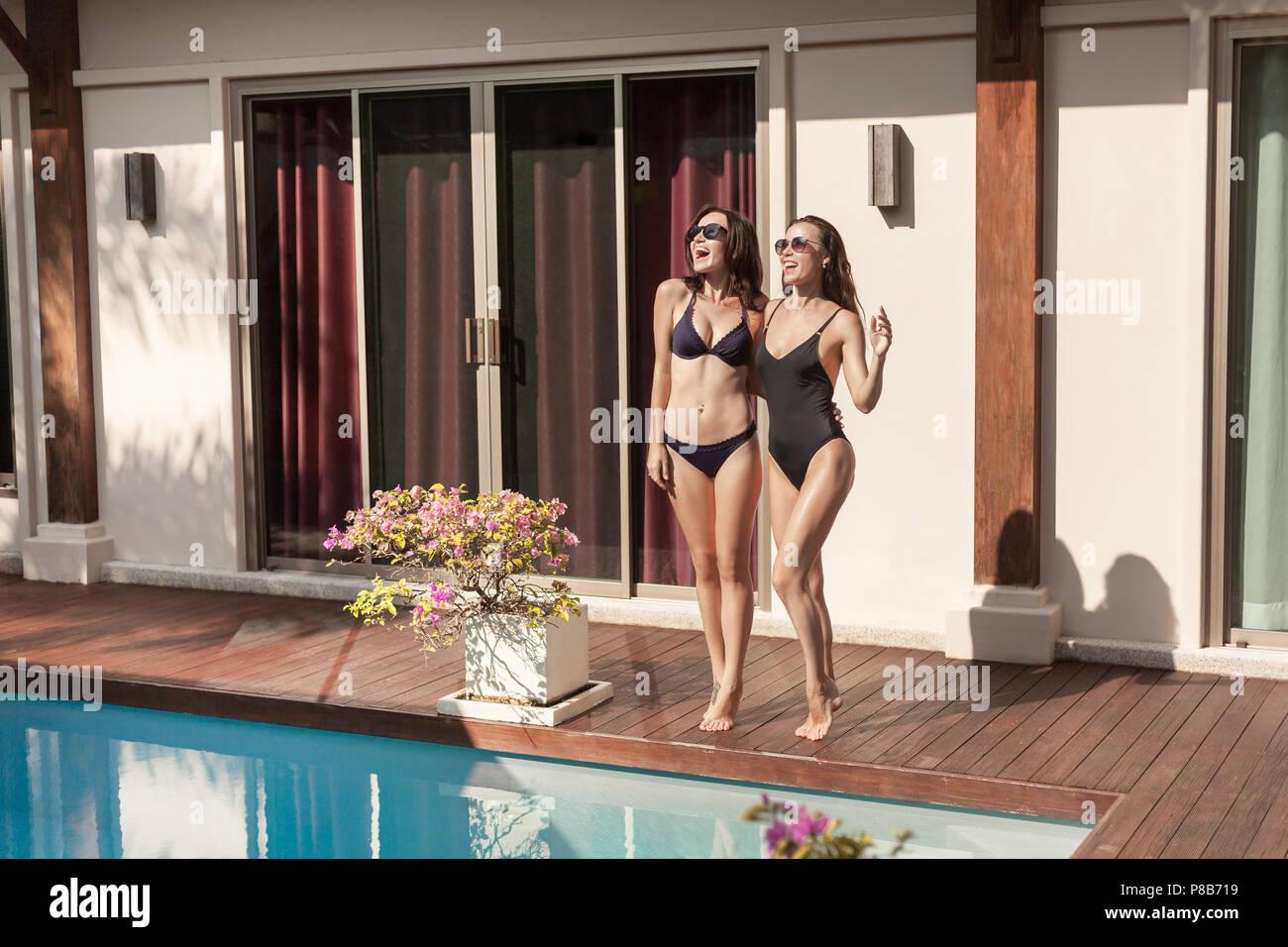 cd8aa15ab5e0 Las mujeres jóvenes y atractivas en bikini y bañador de pie al lado ...