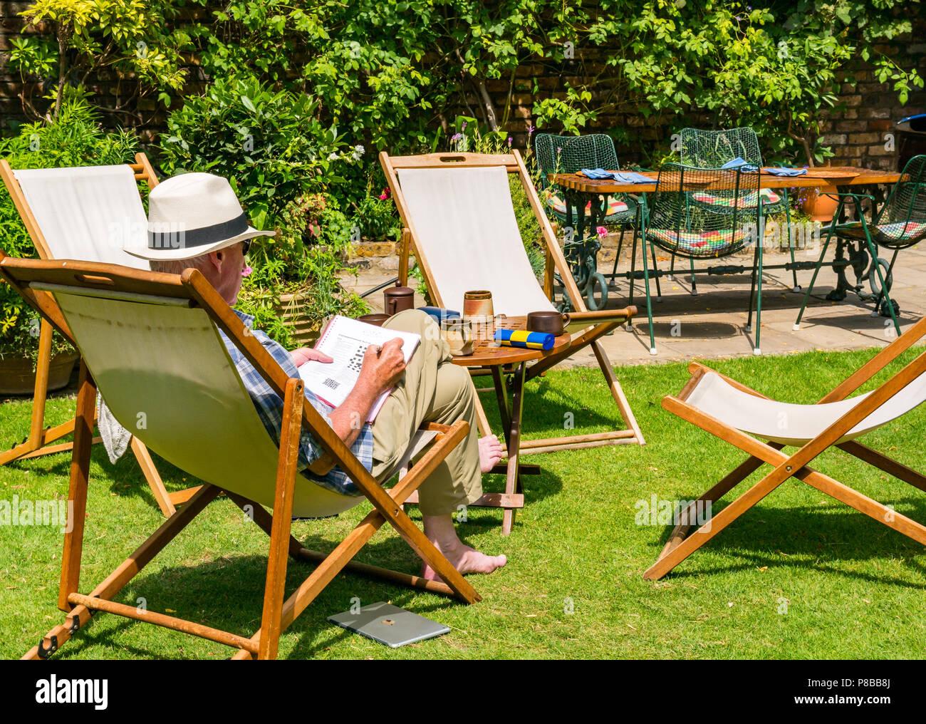 e5f9578ce6245 Más hombre que llevaba sombrero de Panamá resolver crucigramas sentado en  la silla en gran jardín en verano canicular