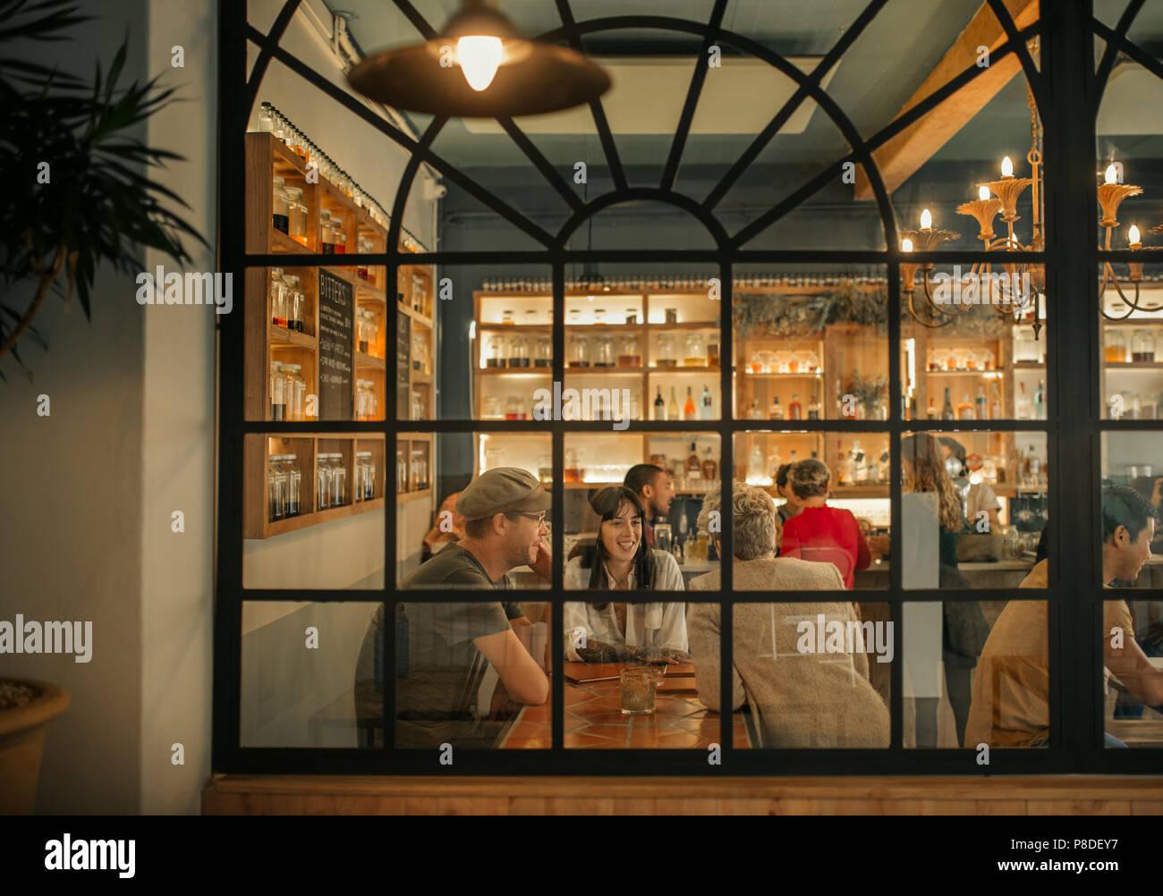 Sonriente joven amigos sentados juntos dentro de un bar de moda Imagen De Stock