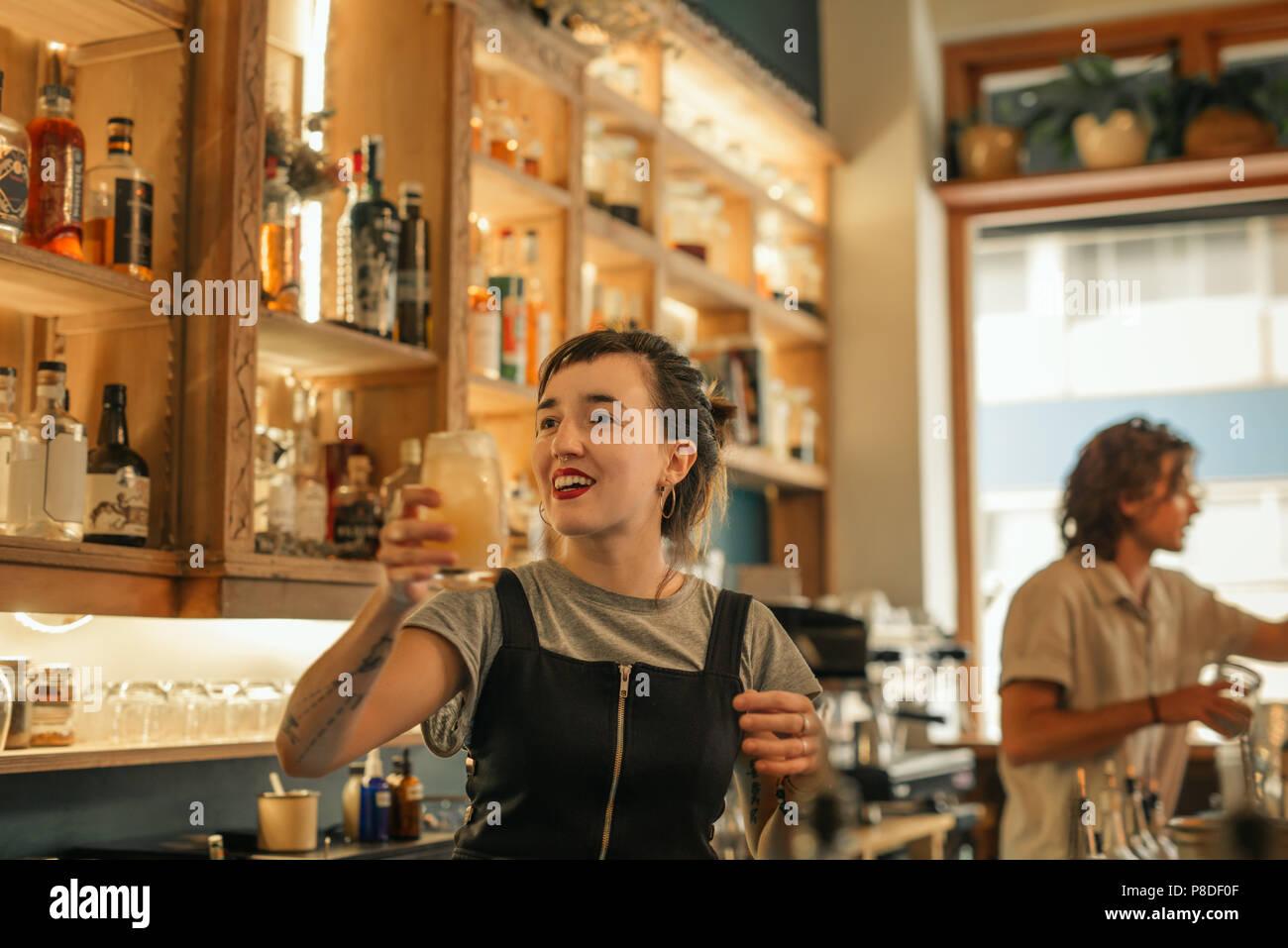 Sonriente joven barman haciendo cócteles en un bar. Imagen De Stock