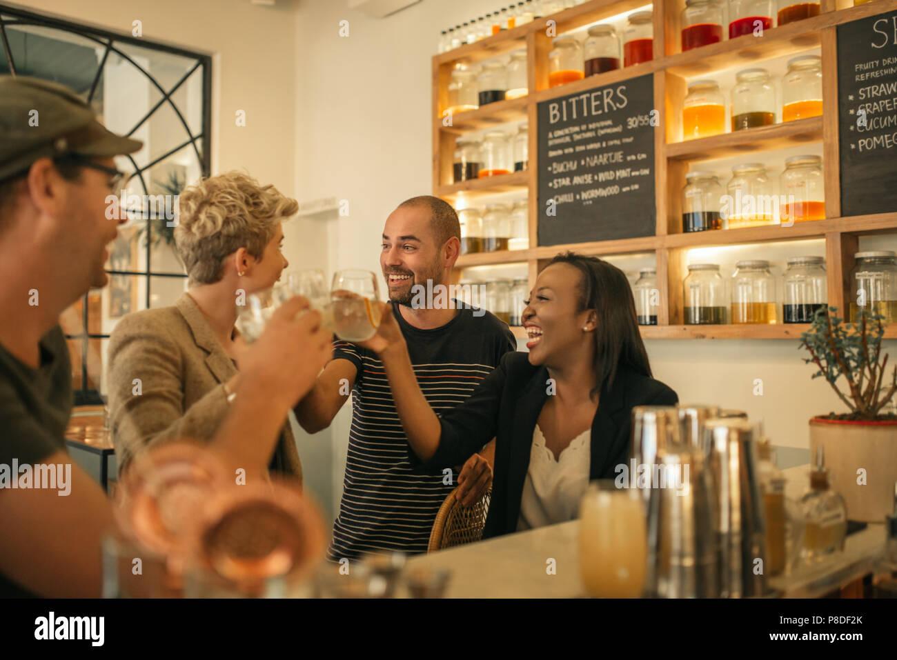 Amigos sonrientes vítores con bebidas en un bar de moda Imagen De Stock