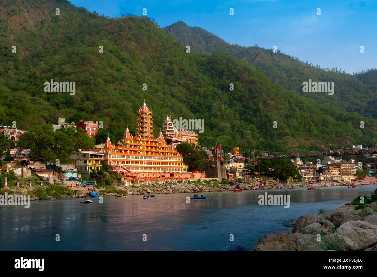 Vista del terraplén del río Ganga, Lakshman Jhula puente y templo, Trimbakeshwar Manzil Tera en Rishikesh Imagen De Stock