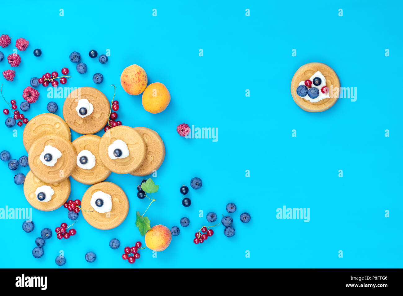 Deliciosa sonrisa mini panqueques con bayas en superficie azul, vista superior. Sentar planas, vista superior alimentos dulces de fondo. Imagen De Stock