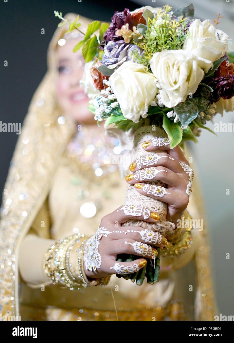 Beautiful Bride manos con tatuaje de henna sosteniendo flores, Indonesia tradición ceremonia de boda Imagen De Stock
