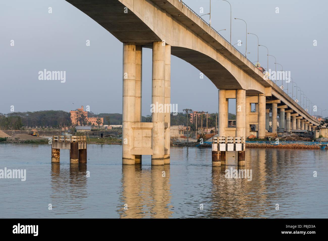 Khulna, Bangladesh, 1 de marzo de 2017: El moderno puente de hormigón en la luz de la tarde conduce a lo largo de un río en Bangladesh Foto de stock