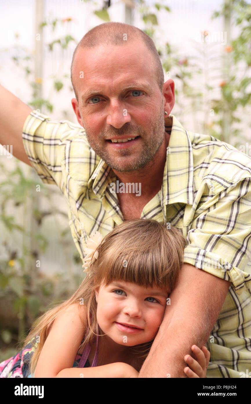 Padre en camiseta amarilla caricias hija infante vestido de púrpura Imagen De Stock