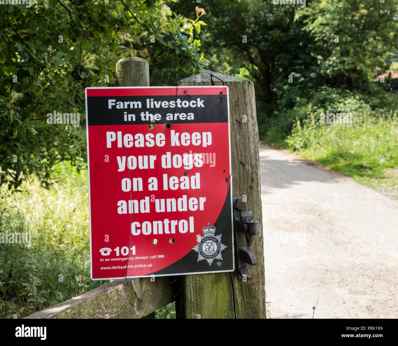 Signo de ganado de granja. Notificación solicitando gente 'Por favor mantenga sus perros a plomo y bajo control', Derbyshire, Inglaterra, Reino Unido. Imagen De Stock