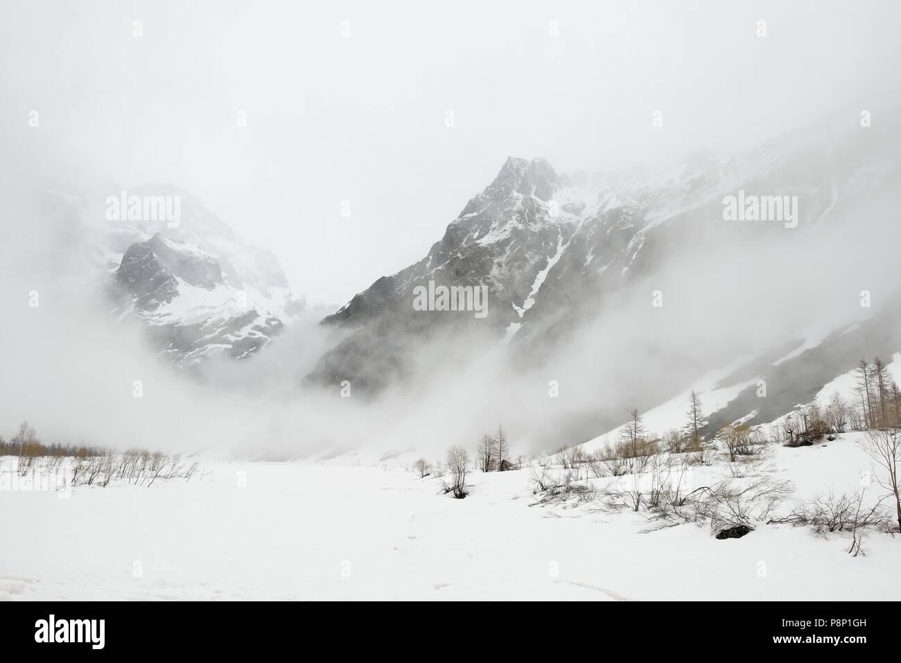 Atmósfera dramática durante la primavera en los Alpes franceses con el derretimiento de nieve y nubes bajas colgantes Imagen De Stock