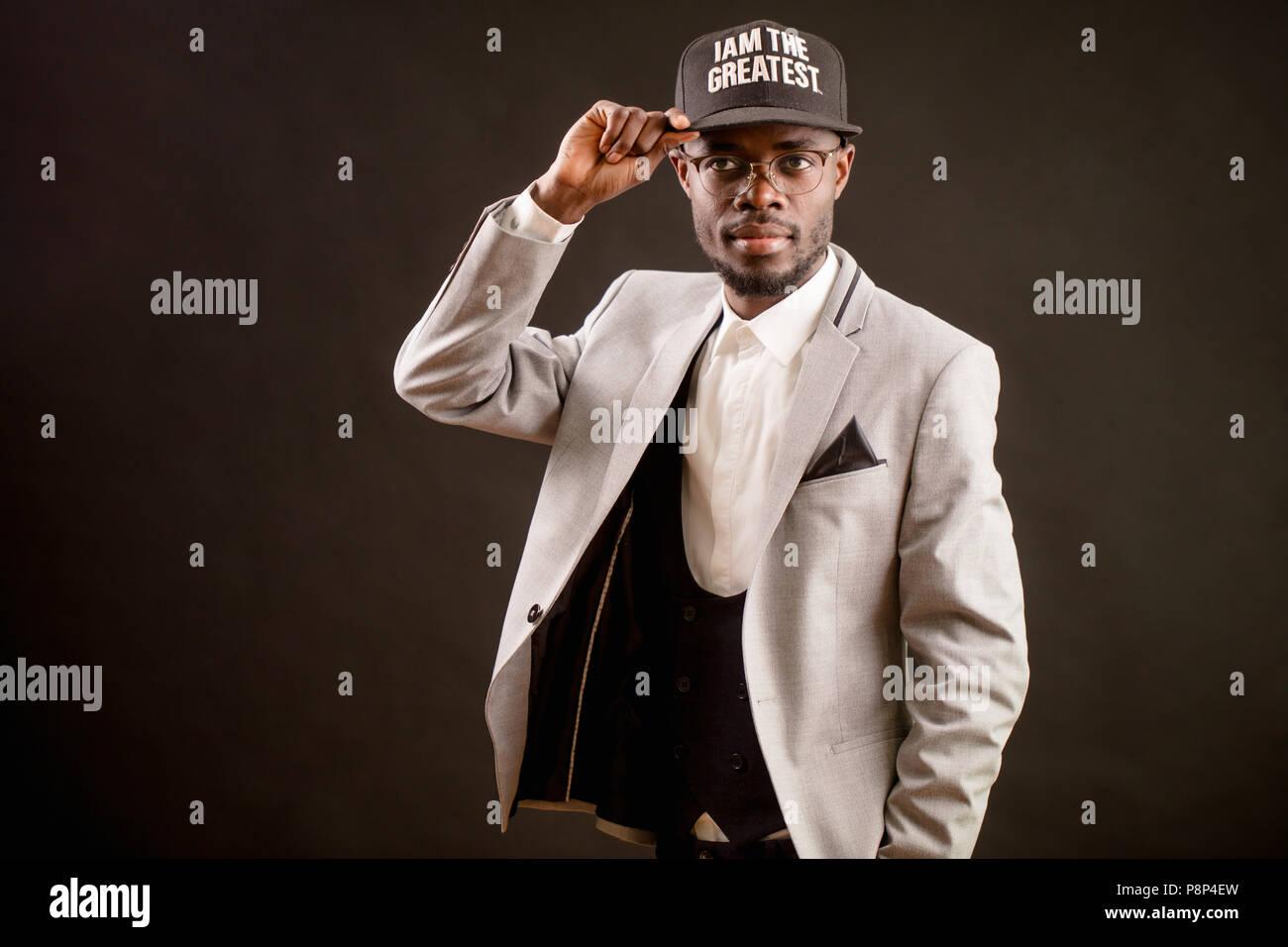 Moda joven hombre africano en un gorro negro y traje blanco aislado sobre  fondo negro. a68768310d1