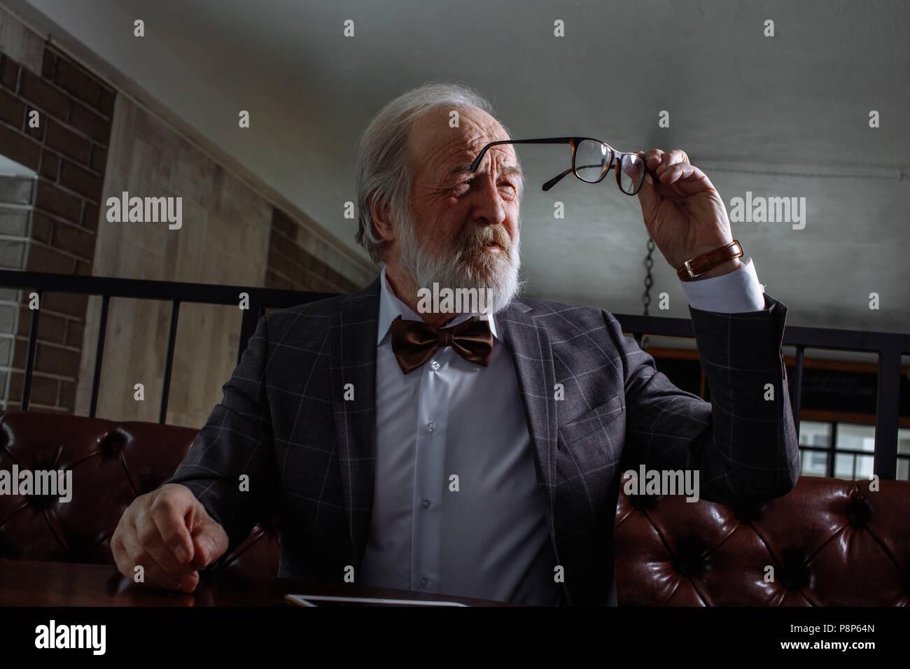 Macho viejo tratando de mirar a través de las sucias gafas. jubilado se está secando vasos. viejo hombre elegante con vista débil Foto de stock