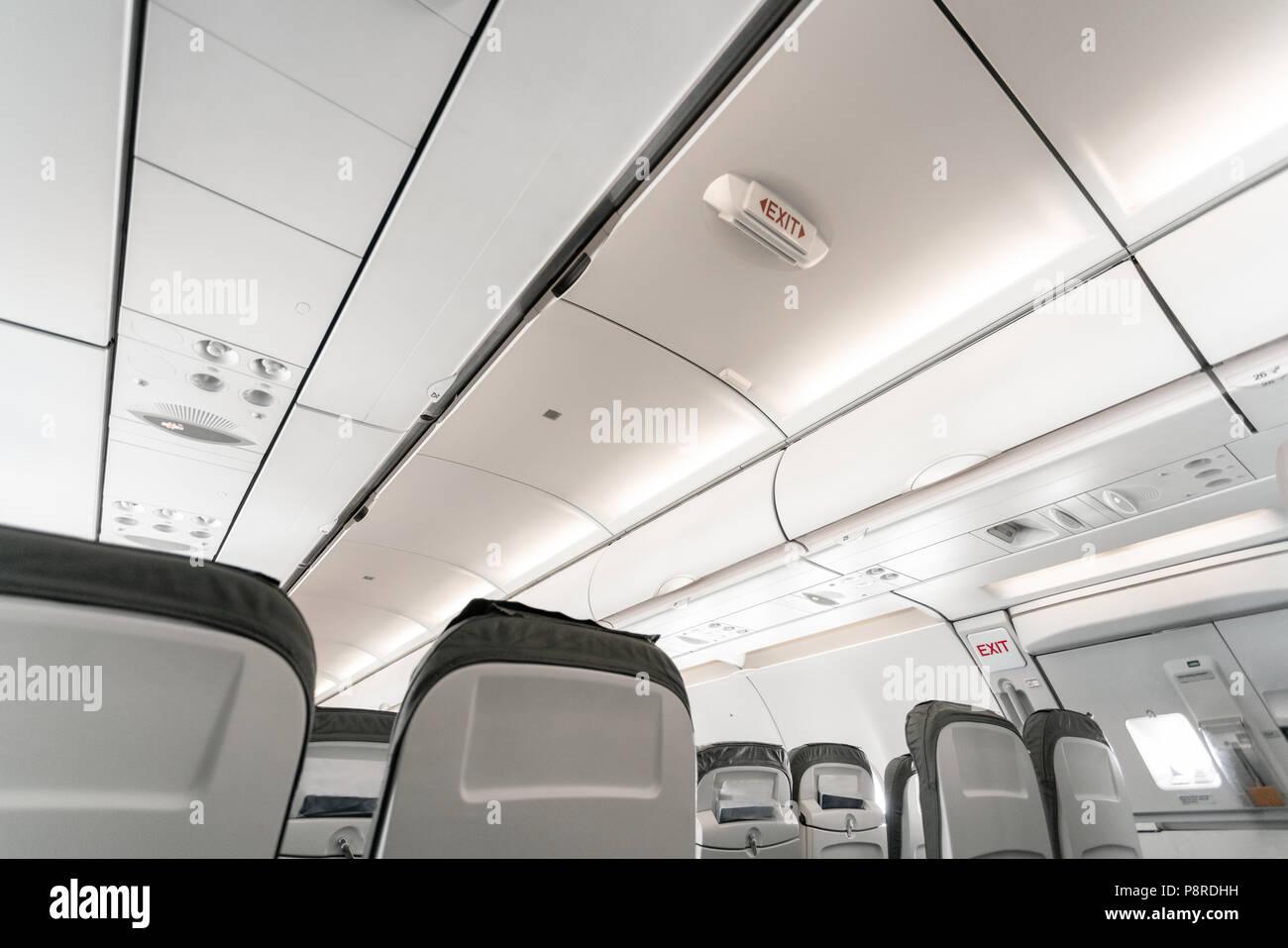 Salida de emergencia en una aeronave, vista desde el interior del avión. Los asientos de los aviones vacíos en la cabina. Concepto de transporte moderno. Los aviones de larga distancia de vuelo internacional Imagen De Stock