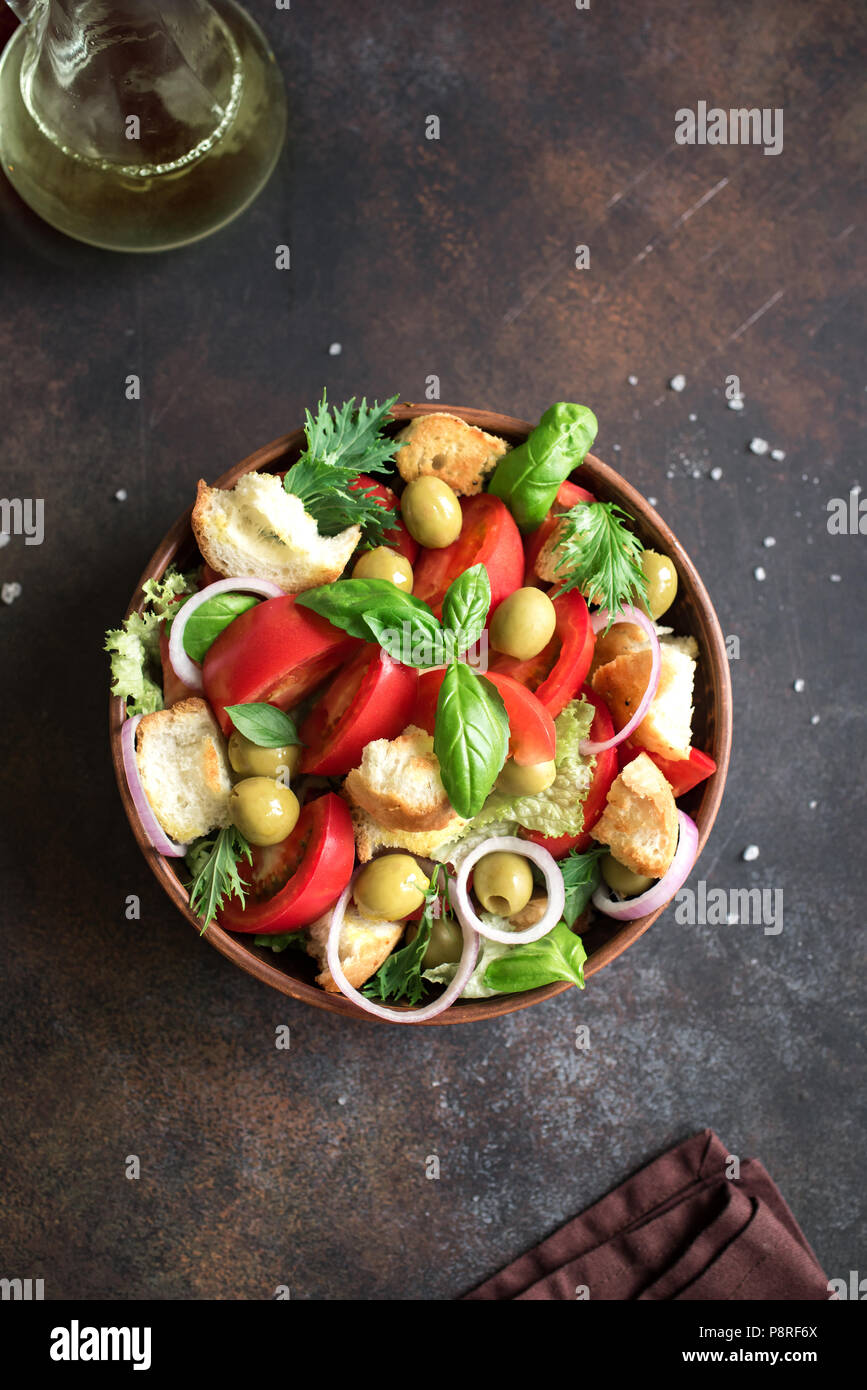 Panzanella Ensalada de tomate con tomates cherry, albahaca y pedacitos de pan ciabatta. Alimentos saludables de verano - ensalada panzanella, vista superior, copia el espacio. Imagen De Stock