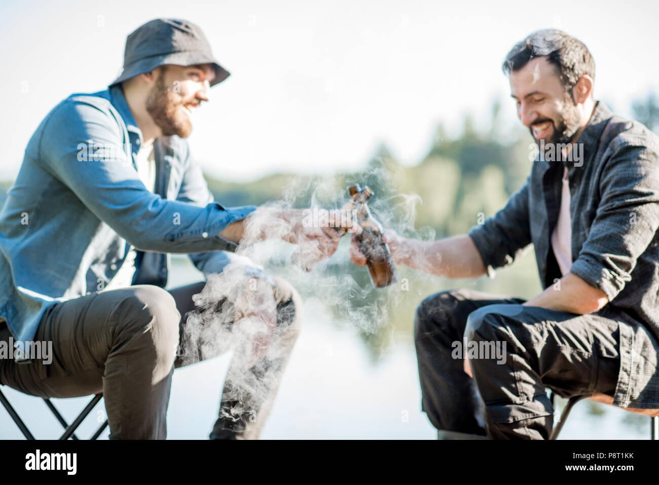 Dos pescadores freír pescado sentados con cerveza durante el picnic en el muelle de madera cerca del lago en la mañana Imagen De Stock