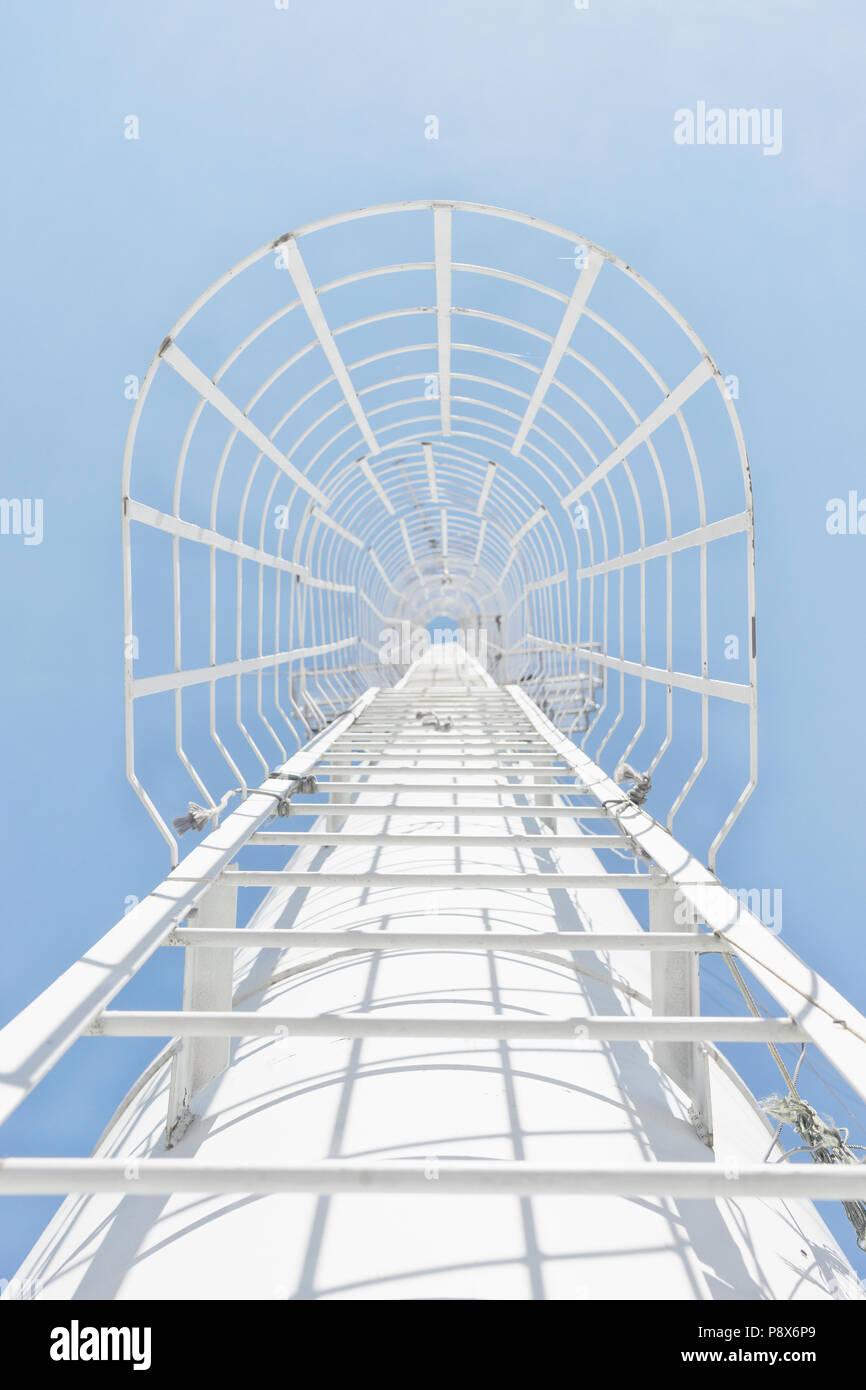 Escalera de hierro blanco en el tubo se levanta en el cielo azul, sin nubes Imagen De Stock