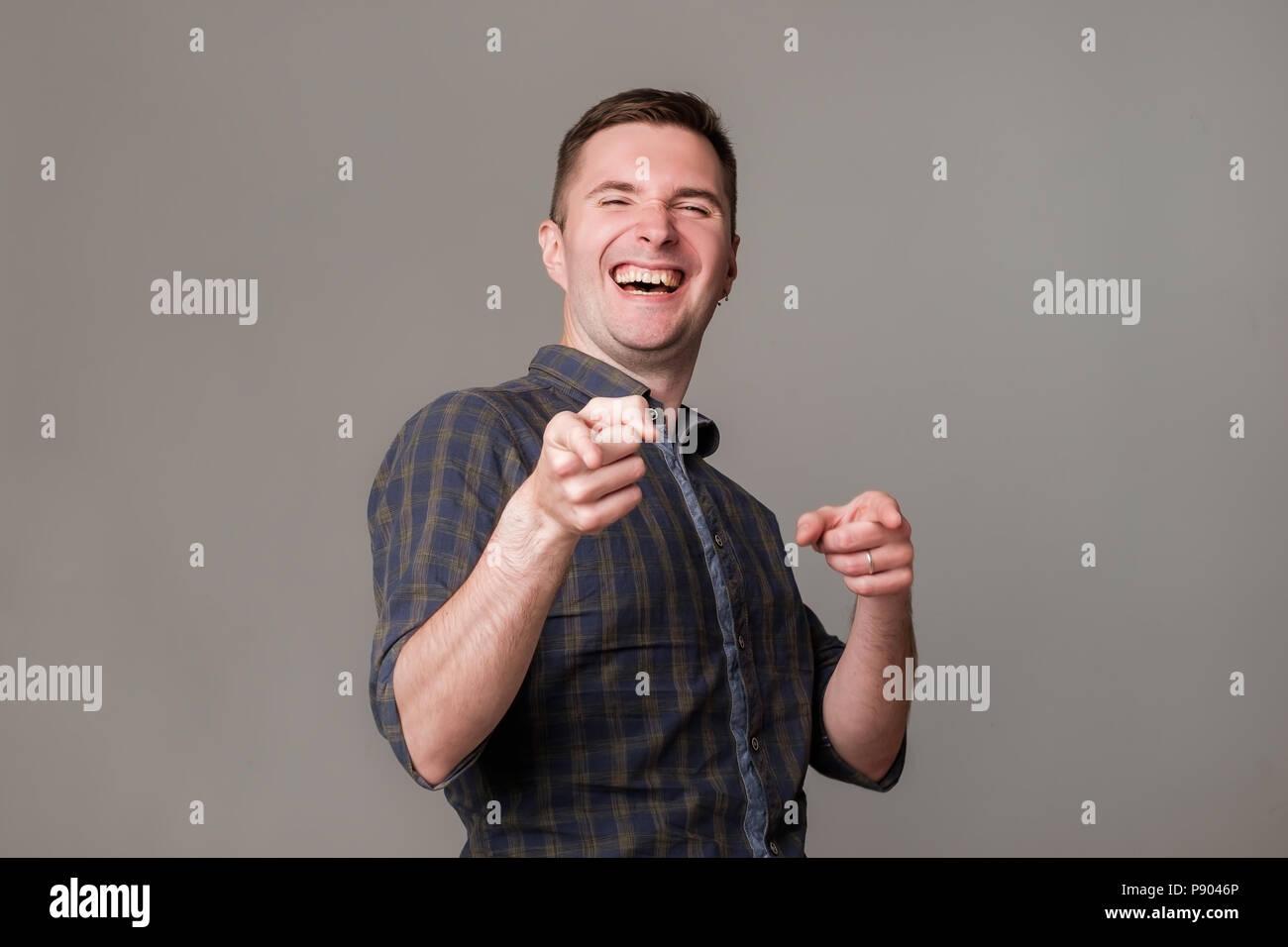 Apuesto joven europeo emocionados sonriendo señalando con el dedo a usted. Imagen De Stock