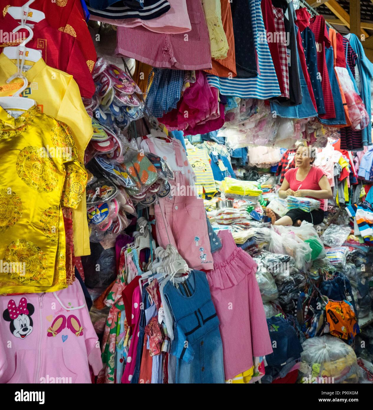 Mujeres Vietnamitas stallholder vendiendo ropa infantil en el bronceado Dinh los mercados de Ho Chi Minh, Vietnam. Imagen De Stock