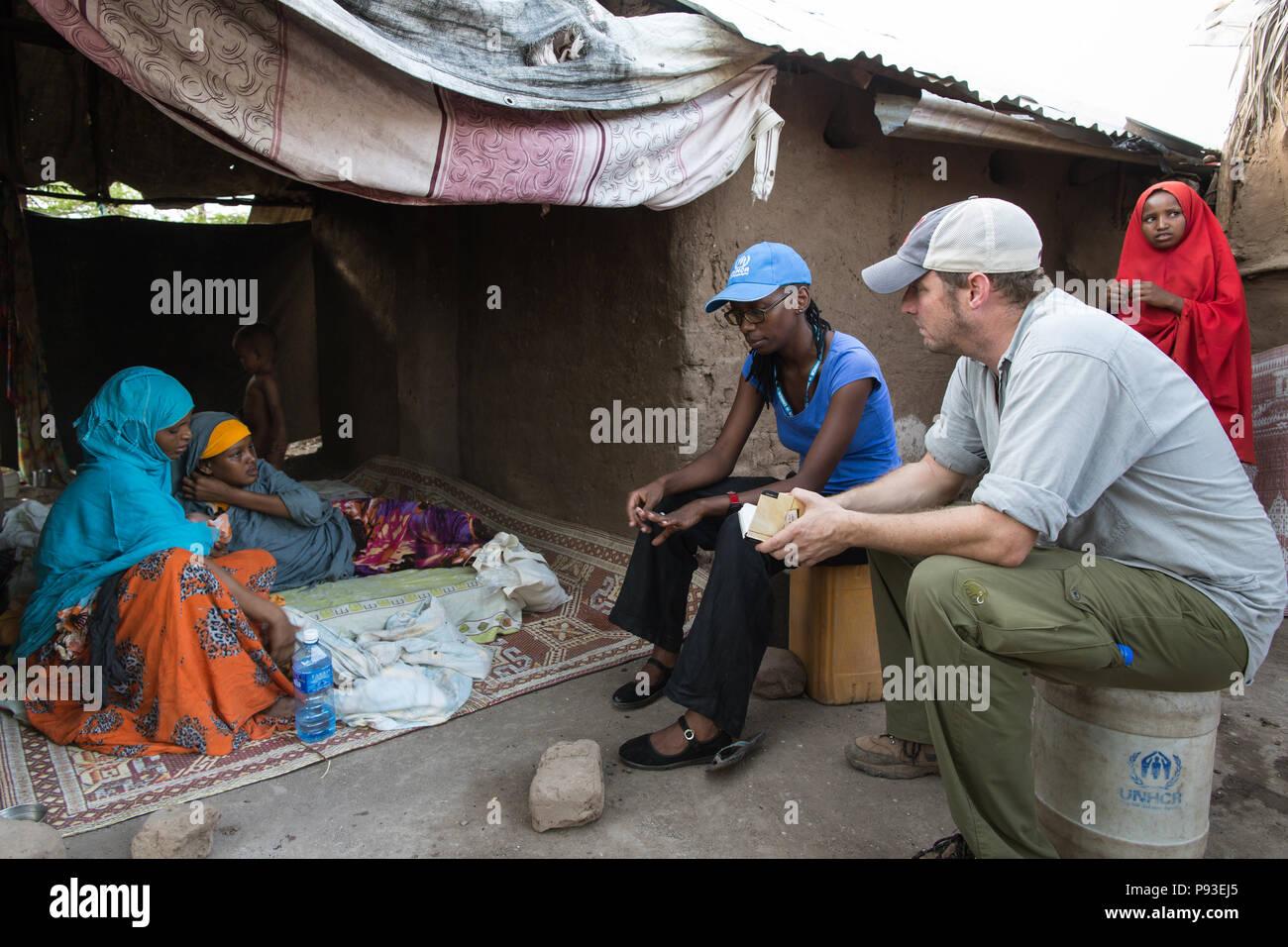 Kakuma, Kenya - Kai Feldhaus, reportero y periodista del periódico Bild en conversación con una familia de refugiados en el campamento de refugiados de Kakuma. Foto de stock