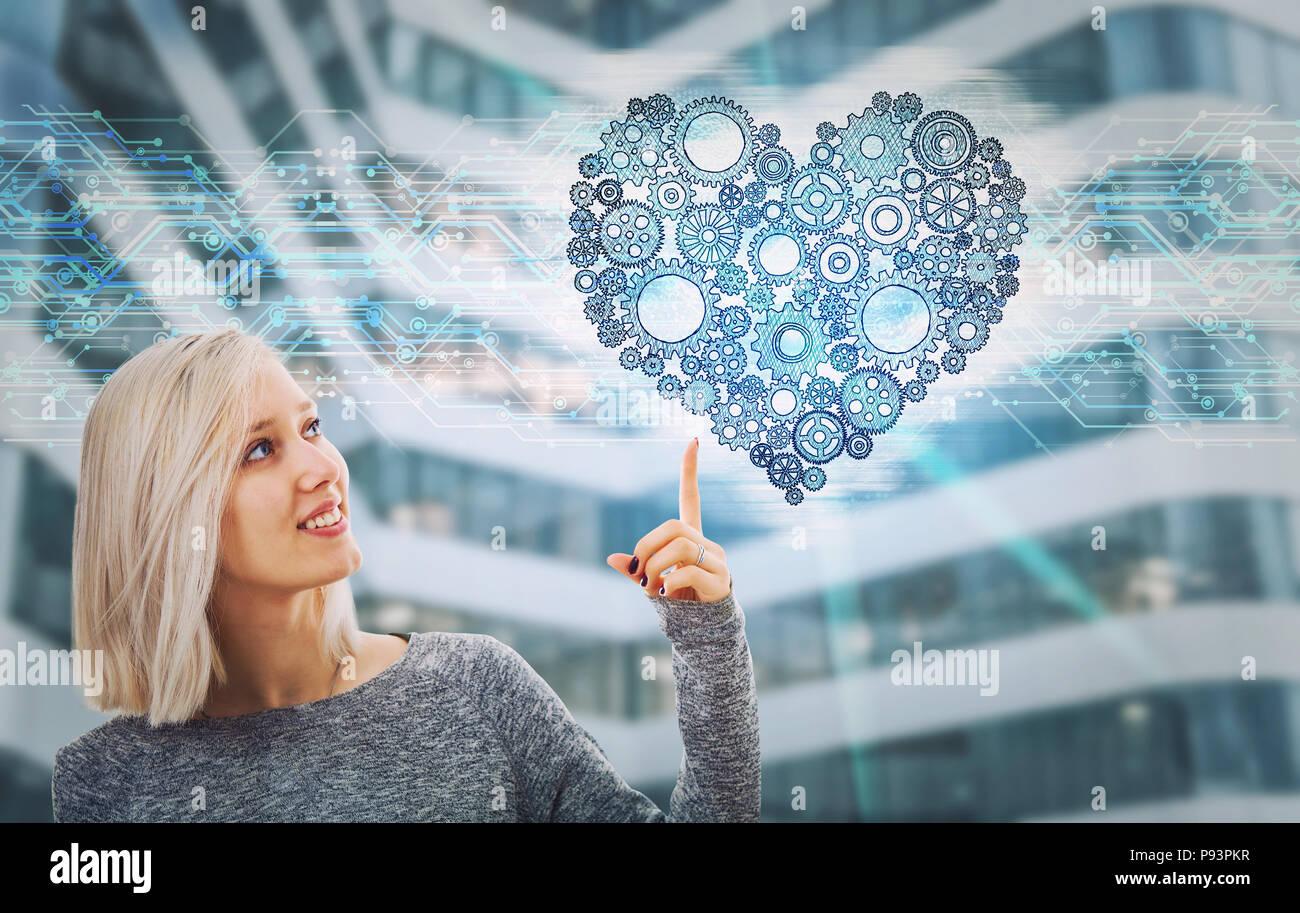 Retrato de mujer sonriente dedo señalador mostrando un engranaje corazón holograma. La tecnología del futuro la inteligencia artificial, la protección de la salud. Derechos caract Imagen De Stock