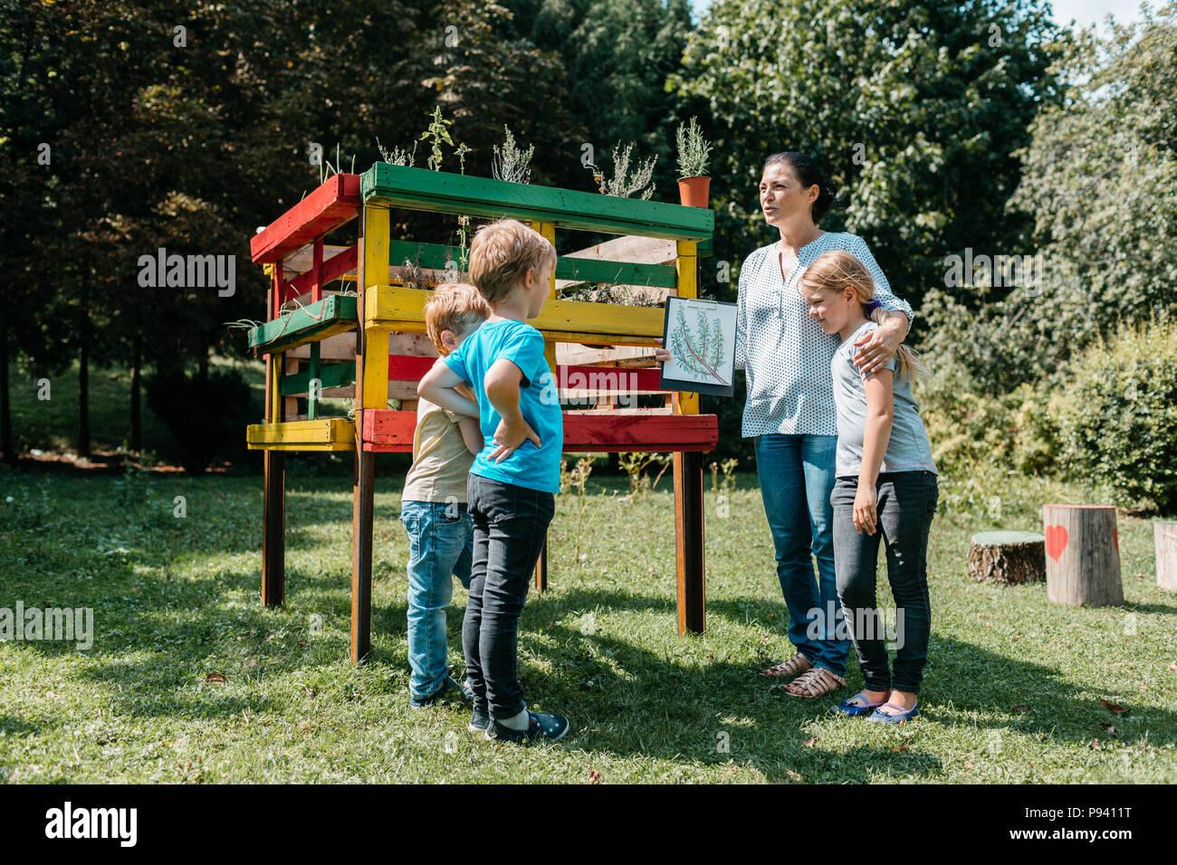 Profesor explicando un tema medioambiental sobre las hierbas a un pequeño grupo de alumnos de primaria. - Los niños de aprendizaje al aire libre discutiendo con un profesor. Foto de stock