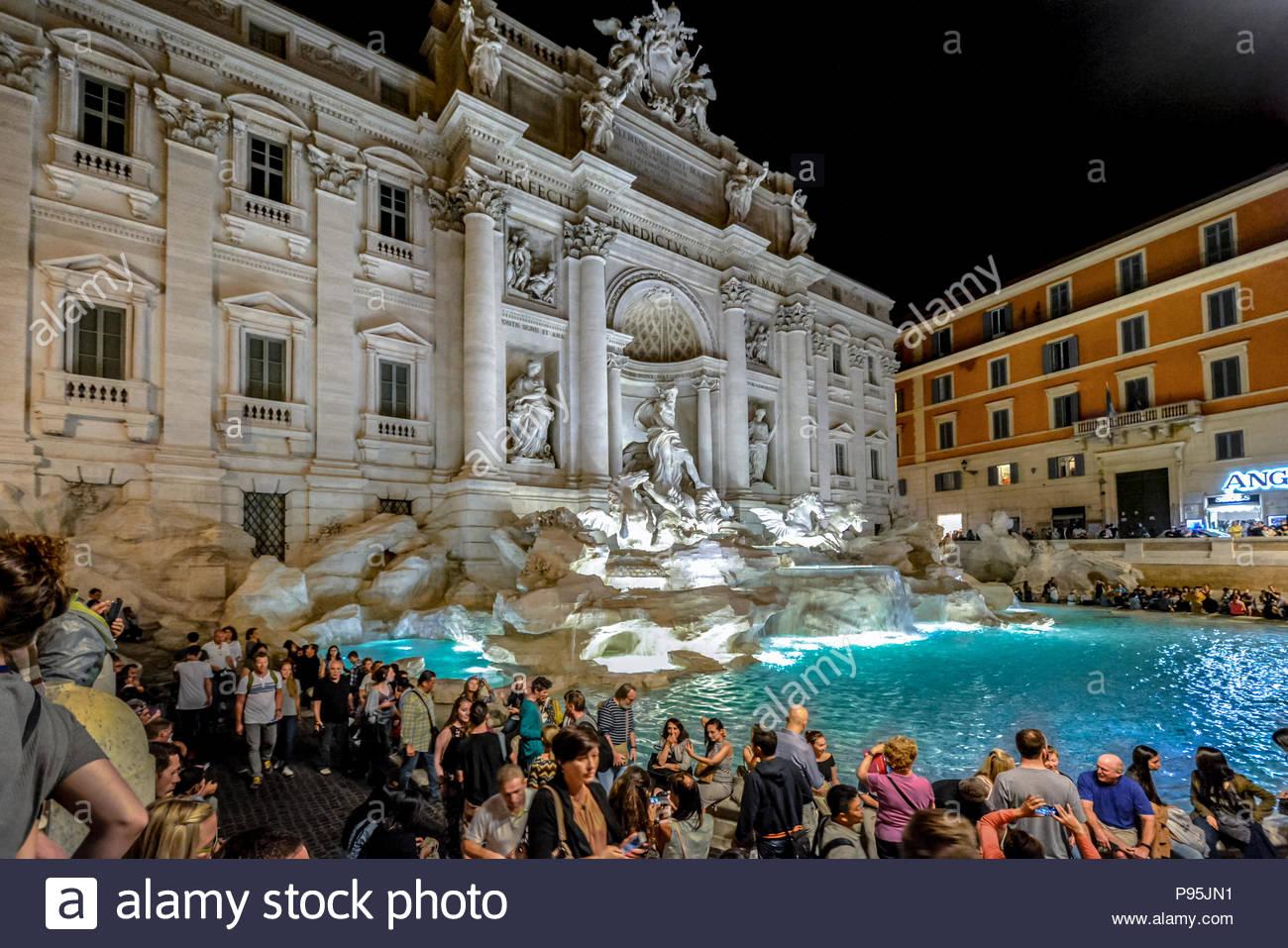 Fuente de Trevi en Roma Italia coloridamente iluminado en la noche con los turistas que lo rodea en una cálida tarde de verano. Imagen De Stock