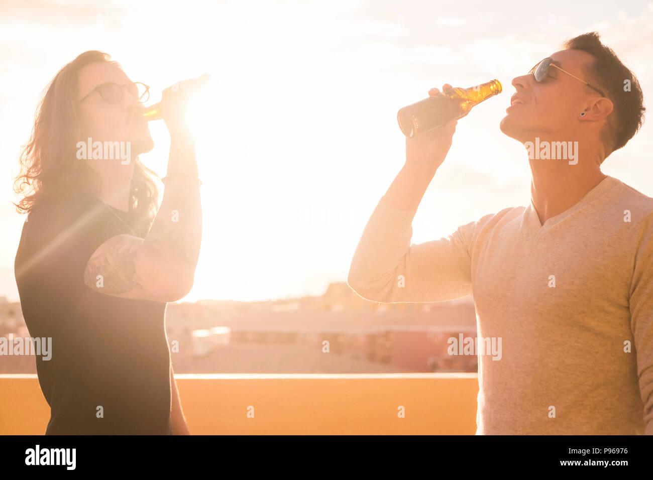 Par de jóvenes bebiendo cerveza juntos bajo el sol del atardecer. imagen brillante para machos hermosos modelos de felicidad y de actividad de ocio al aire libre Imagen De Stock
