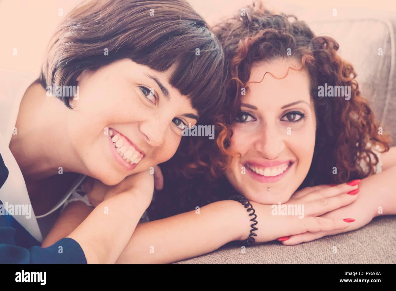 Buen tiempo y felicidad con risas y sonrisas para dos amigos caucásicos sentar juntos en el sofá en casa. La amistad Concepto de imagen interior w Imagen De Stock