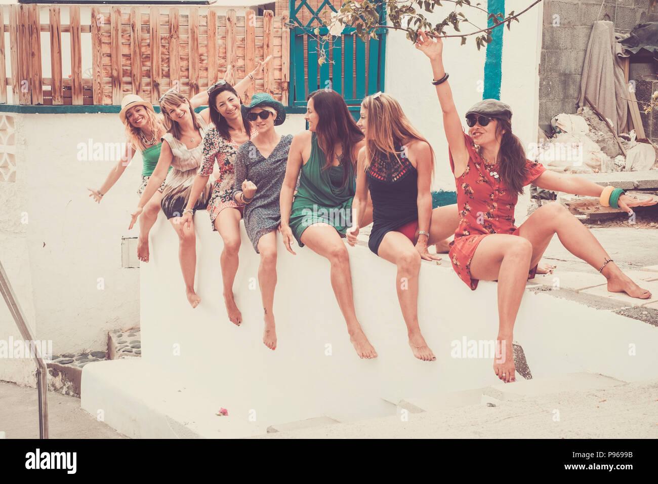 Grupo de siete jóvenes sonrisa hermosa mujer loca en vacaciones y amistad o relación permanecer juntos a sentarse y volverse loco con la risa. verano col Imagen De Stock