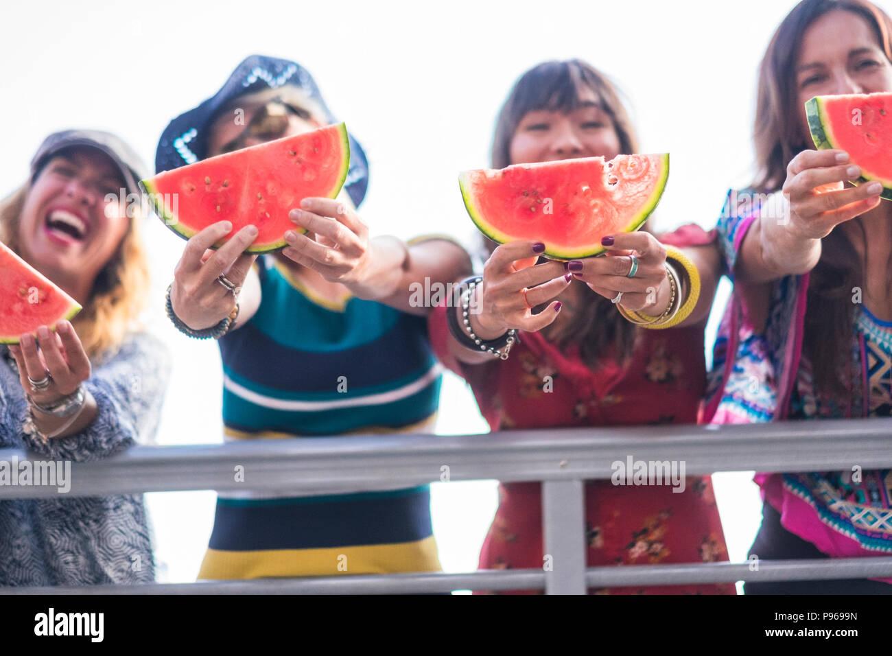 Cuatro hembras jóvenes caucásicos bonito felices comiendo sandía para celebrar el verano y cálido día con sun, cerca del océano. Hermosos colores para el grupo de Imagen De Stock