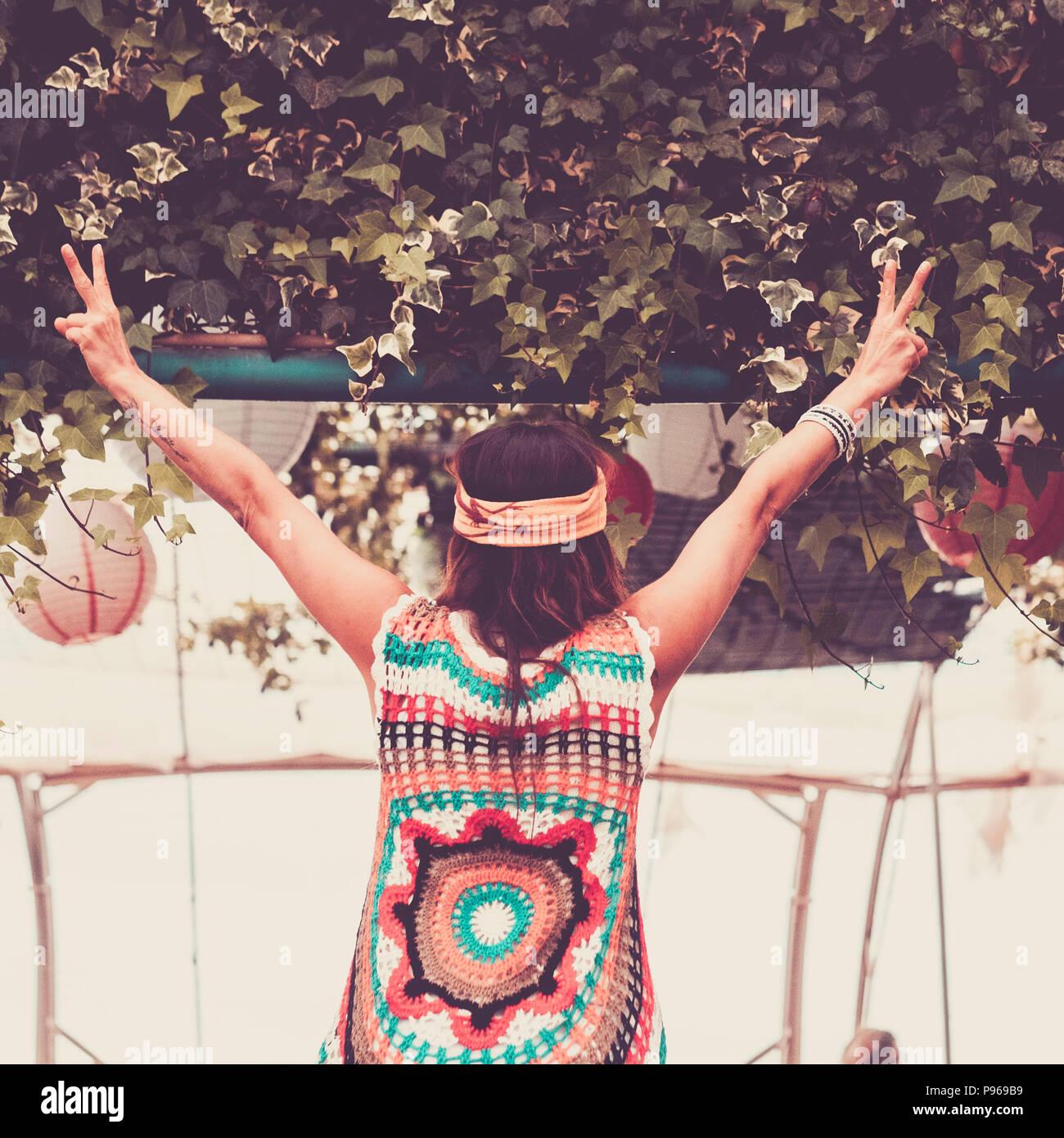 Imagen concepto ganador con libertad chica visto desde atrás abriendo los brazos y abriendo los dedos. ropa hippie como en los años '60. Imagen De Stock