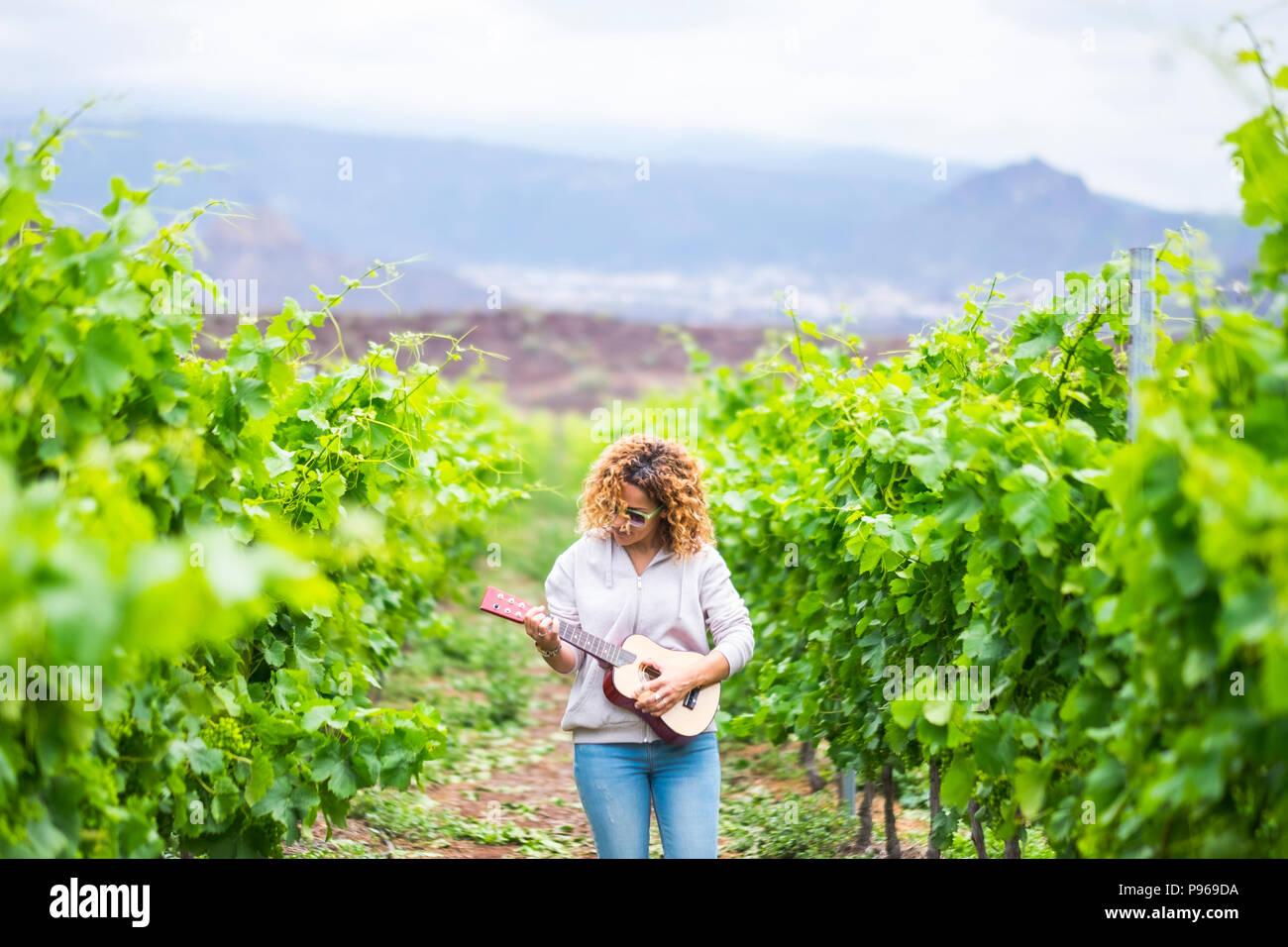 Piscina señora tocando un ukelele guitarra acústica en el viñedo. artista en el trabajo crea una nueva canción y disfrutar de las actividades recreativas con música. beau Imagen De Stock