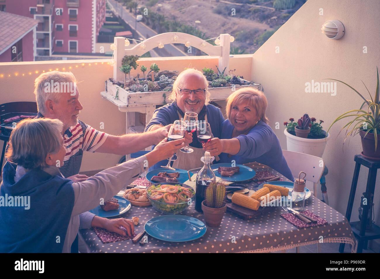 Grupo de adultos caucásicos personas maduras comiendo y bebiendo juntos celebrando el evento por la noche en la terraza con vista de la ciudad y la naturaleza en verano. Imagen De Stock