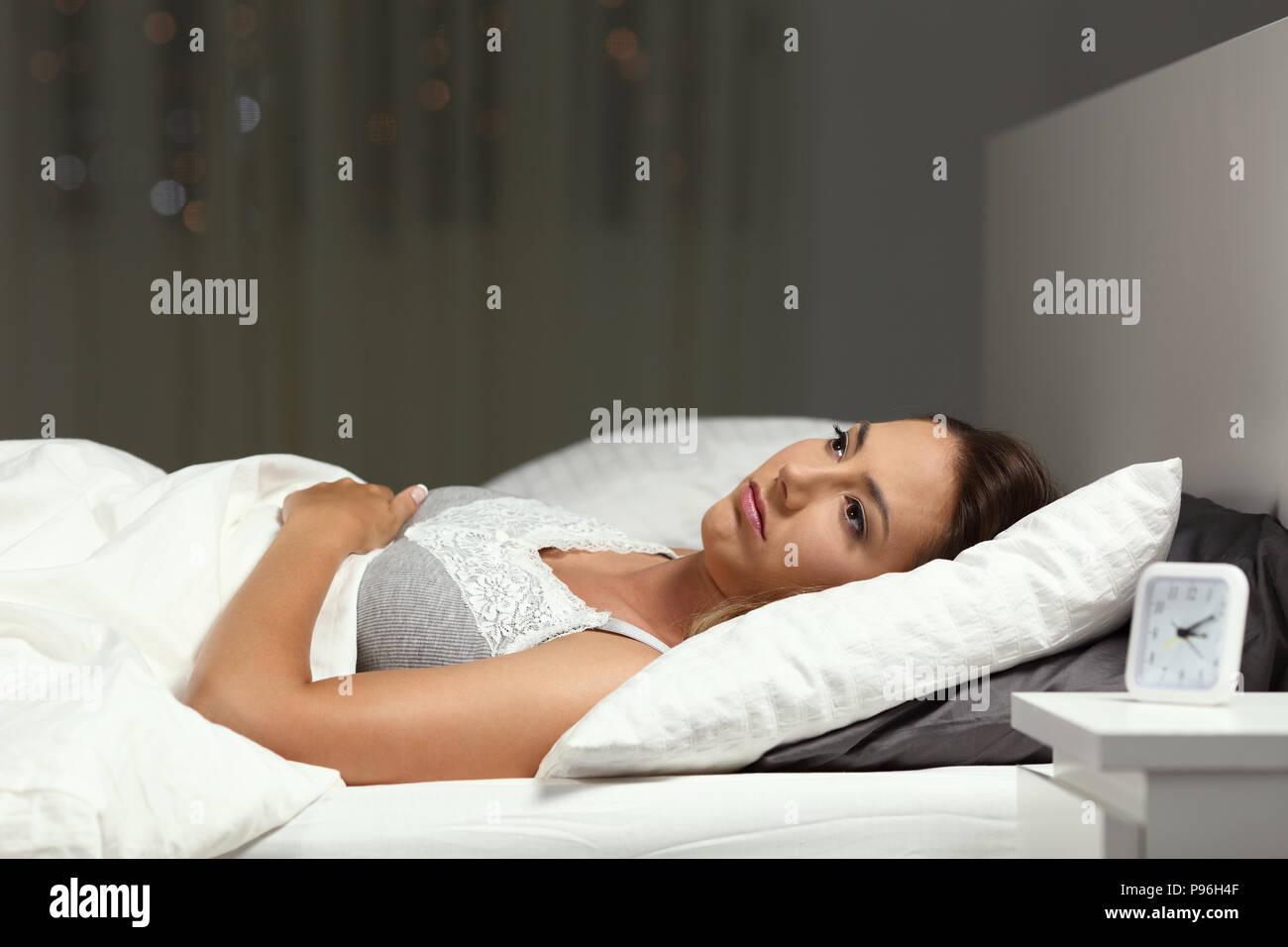 Insomniac mujer incapaz de dormir acostado en una cama en la noche en su domicilio. Foto de stock