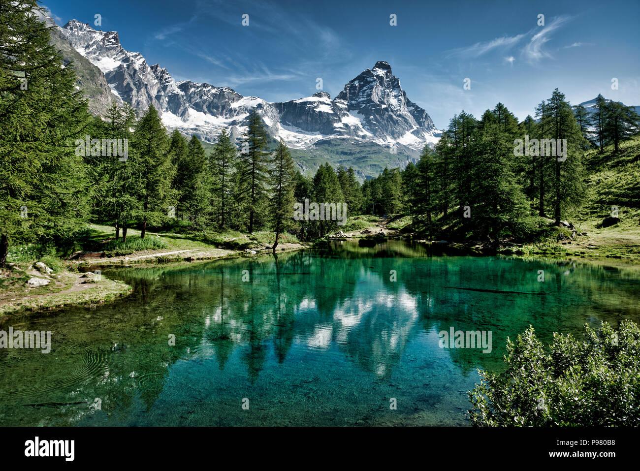 El lago azul y el Matterhorn en un pintoresco paisaje de verano con luces de Sol visto desde Breuil-Cervinia, Valle de Aosta - Italia Imagen De Stock