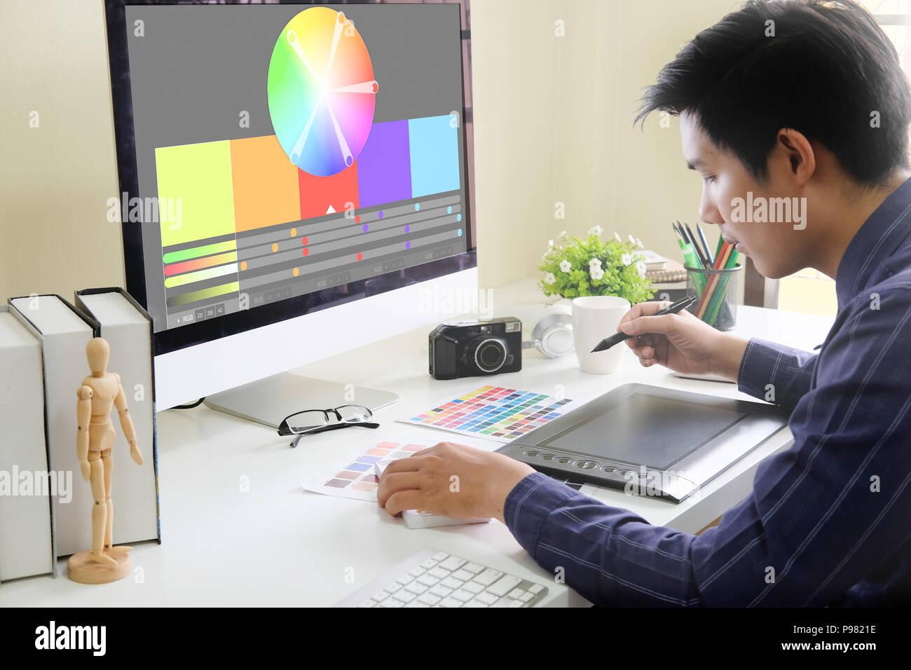 Diseñador gráfico que trabaja en tableta digital en el lugar de trabajo creativo. Foto de stock