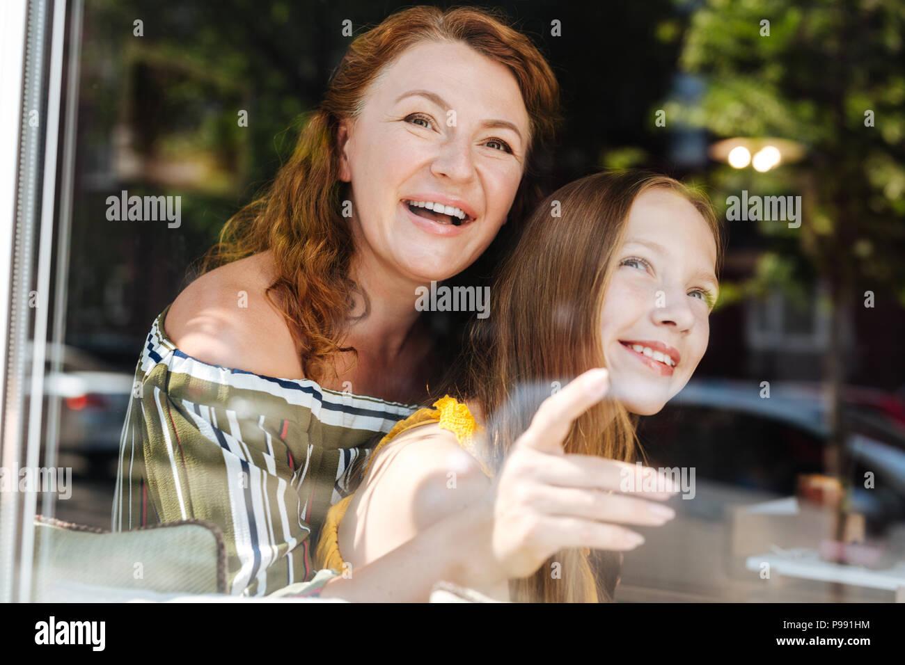 Cuidando la transmisión madre abrazando a su hija atractiva Imagen De Stock