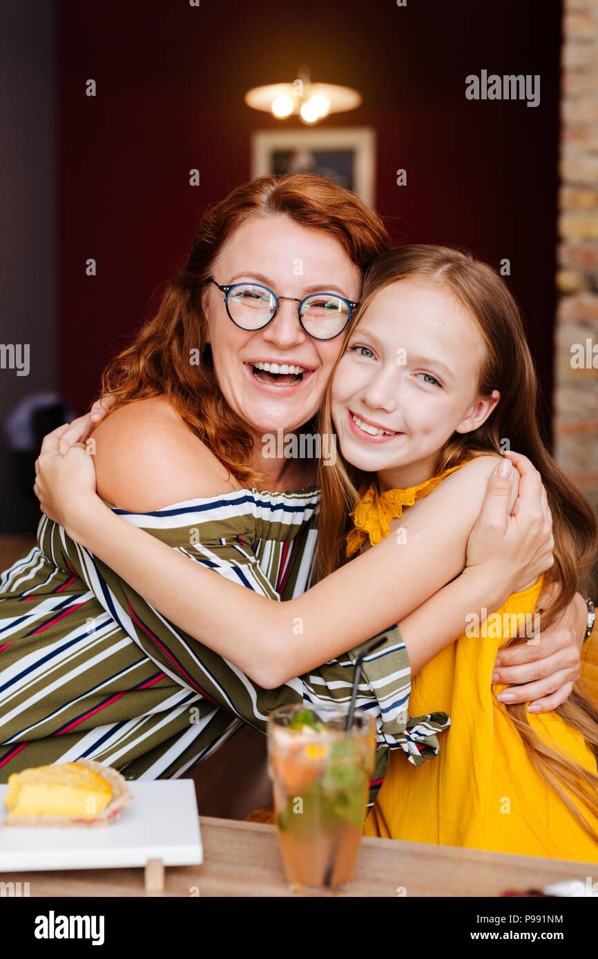 Laughing mujer con cabello ondulado abrazando a su niña Foto de stock
