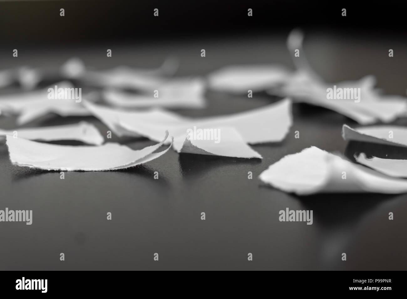 Rip en muchos pedazos de papel sobre una superficie negra Foto de stock