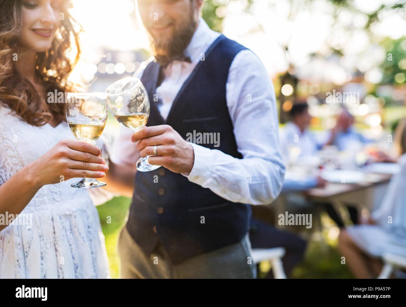 La novia y el novio vasos tintineo en la recepción de la boda fuera en el patio. Imagen De Stock