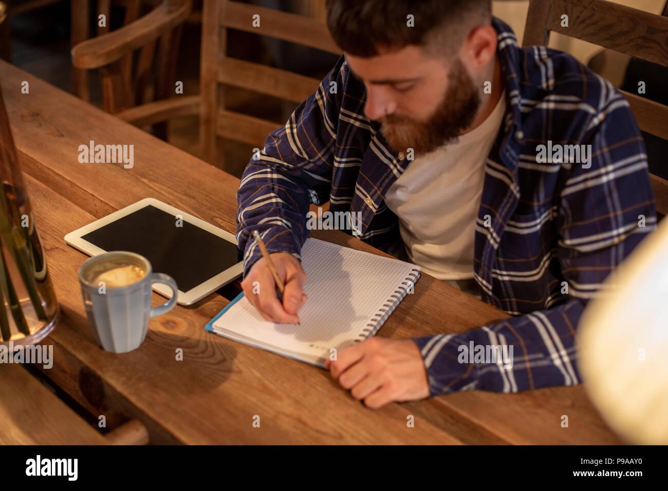 Empresario joven barbudo se asienta en el café, en casa frente a la mesa y escribe en el bloc de notas, se encuentra cerca de la tablet PC con pantalla negra. El hombre está trabajando, estudiando. Imagen De Stock