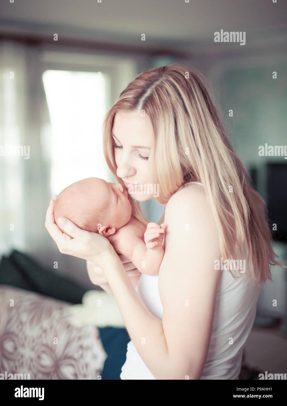 Feliz madre sosteniendo a un niño recién nacido Foto de stock