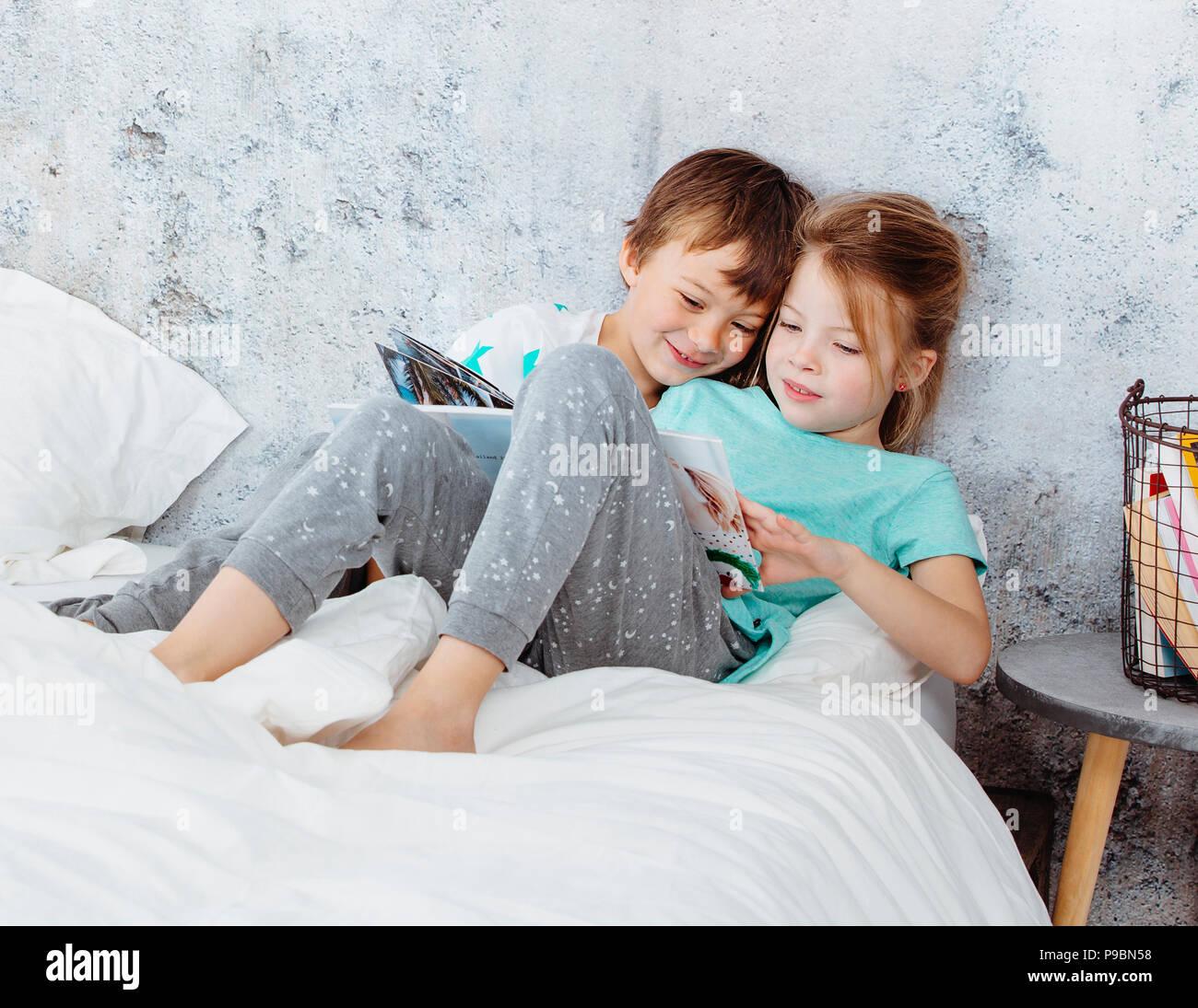 Hermosa chica está leyendo un libro a su hermano en la cama Imagen De Stock