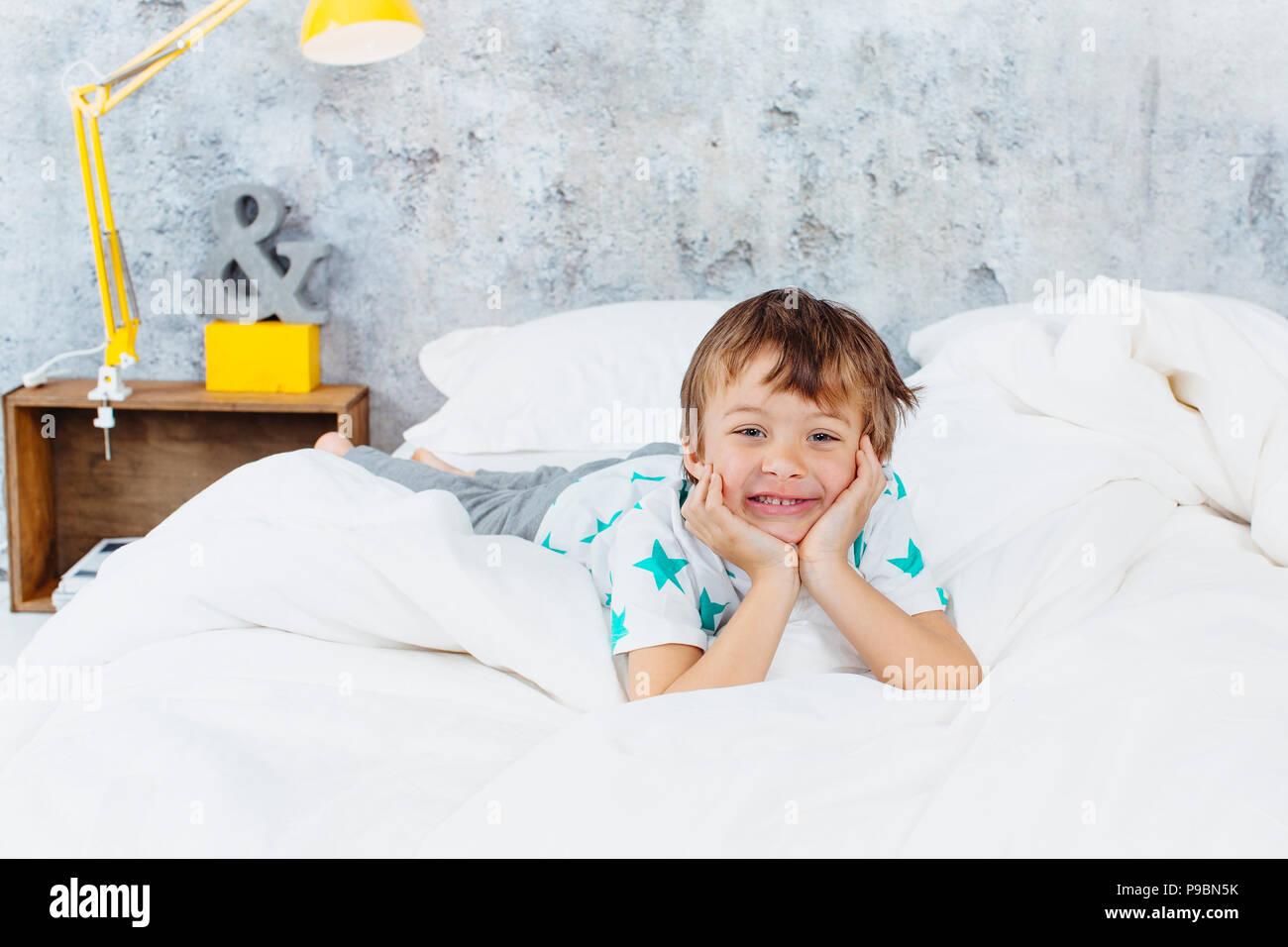 Precioso dormitorio - hermoso muchacho está en la cama Imagen De Stock
