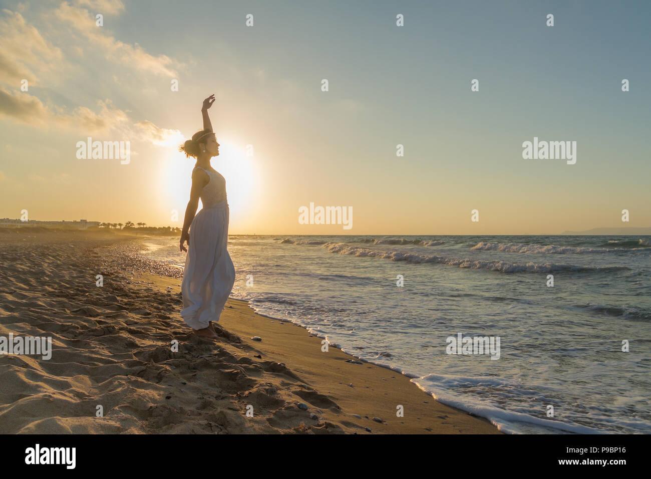 Mujer con los brazos levantados, descalzos, sentirse feliz, vivo y libre en la naturaleza meditando en sandy Misty Beach respirar aire fresco del océano limpio al anochecer. Vacaciones de verano concepto de estilo de vida Imagen De Stock
