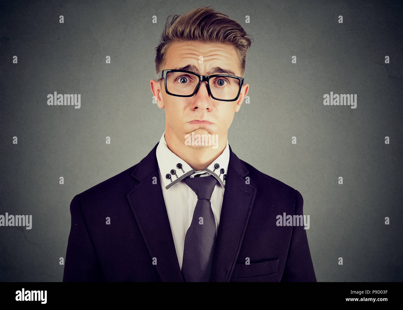 Joven Hombre formal en traje y gafas mirando insultados y lástima ceño fruncido y llorando sobre fondo gris Imagen De Stock