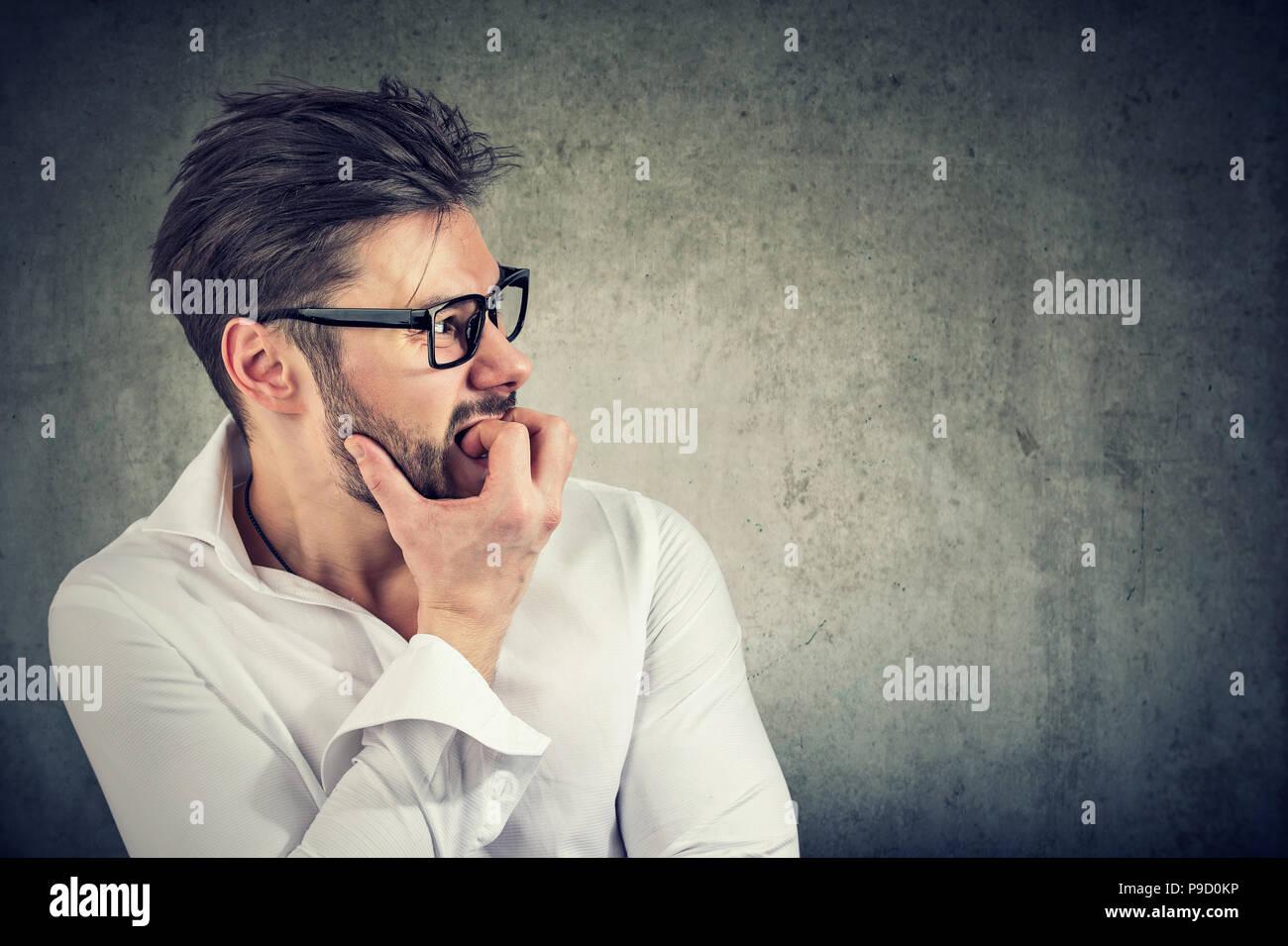 Adulto hombre barbado tener pánico y fobia mirando a otro lado mientras muerde las uñas en ansiedad sobre fondo gris Foto de stock