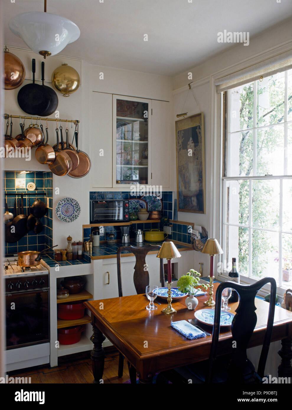 Pequeña mesa para comer en una casa con cocina vintage sartenes de ...